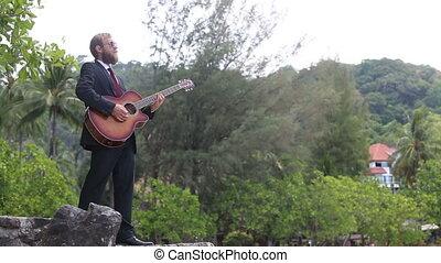 guitarist gesticulates against tropical trees
