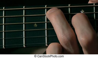 Guitarist hand touching strings on fretboard. Music...