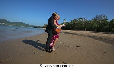 guitarist helps blonde girl play guitar