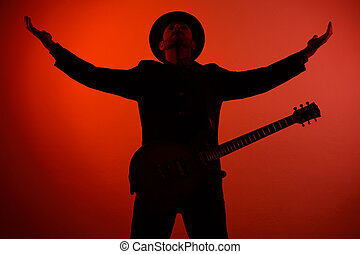 guitarist in a hat is standing with his arms outstretched