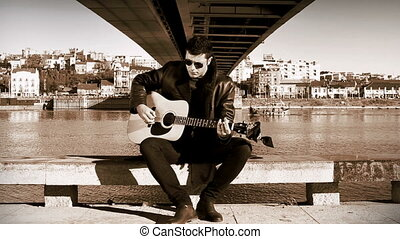 Guitarist in retro style playing under the bridge with view...