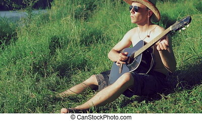 Guitarist in sunglasses and hat playing the guitar on the beach. 4k