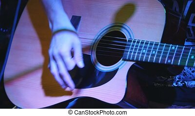 Guitarist is holding acoustic guitar at concert in club