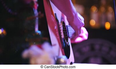 Guitarist is holding acoustic guitar near microphone at concert in club, extremely close up