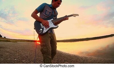 guitarist musician man playing a solo on electric guitar by the river at sunset sky clouds  color