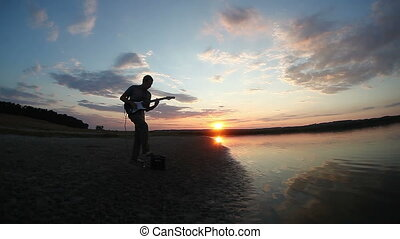 guitarist musician playing electric guitar at sunset by the water of the river waves sun sets piroda music