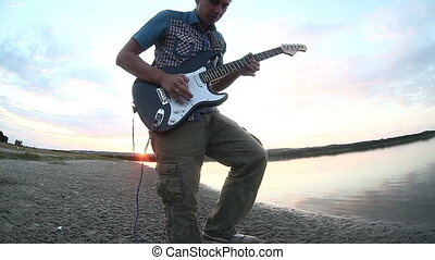 guitarist musician playing electric guitar at sunset by water of the river waves sunsets piroda music sunlight