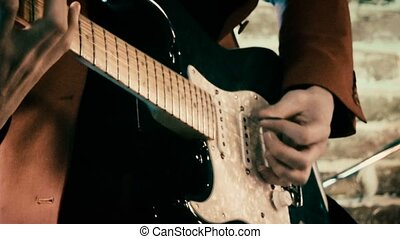 Guitarist on stage playing guitar and singing in front of brick wall defocused footage