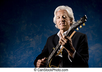 Guitarist with his Instrument in front of a Blue Wall