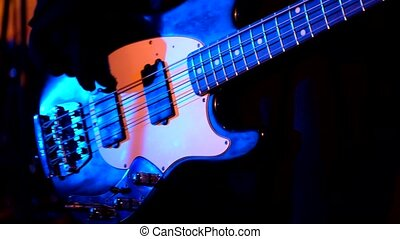 Guitarist playing bass guitar at live concert in night club