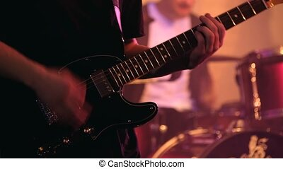 Guitarist playing electric guitar at live concert in night...