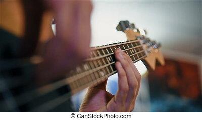 Guitarist Playing On Electrical Bass Guitar. Close Up