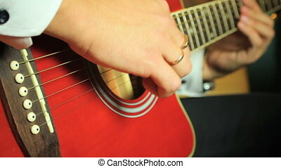 Guitarist playing on six-string acoustic guitar. Close up of...