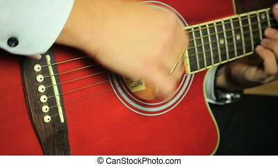Guitarist playing on six-string acoustic guitar. Close up of hands and guitar strings.