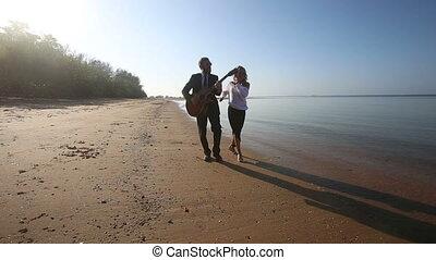 guitarist plays and blonde girl dances walking along beach
