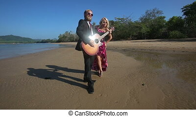 guitarist plays and blonde girl flirts posing in low tide