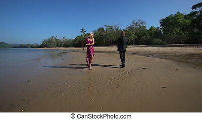 guitarist plays and girl dances they walk round under low tide