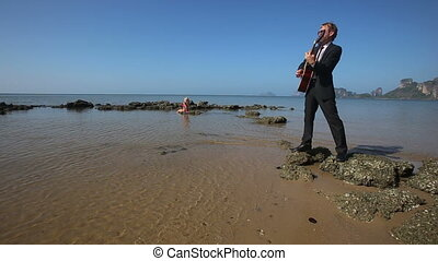 guitarist plays emotionally on beach  girl sits on rock in sea
