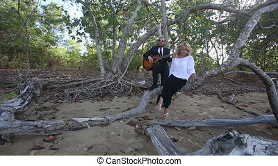 guitarist plays for blonde girl sitting on branch at trees