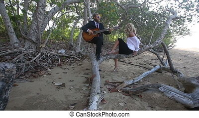 guitarist plays for girl she lies down on branch of tree