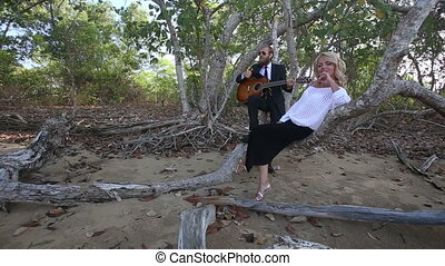 guitarist plays for girl she smiles and laughs at tropical trees