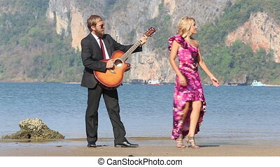 guitarist plays girl dances in front of near sea and cliffs