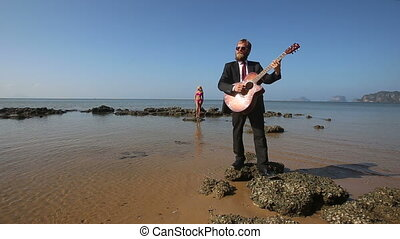 guitarist plays masterly on rock at beach for blonde girl