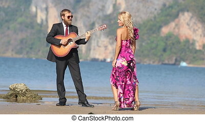 guitarist plays not looking at dancing girl against cliffs