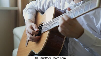 guitarist plays on acoustic guitar at home
