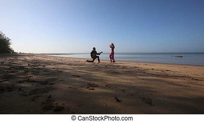 guitarist plays on knee girl dances under fast camera on beach