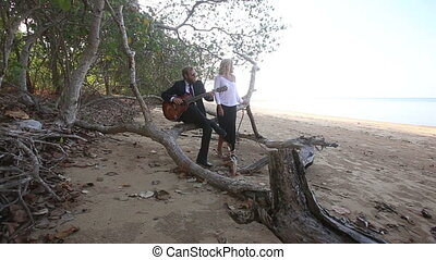 guitarist plays sitting on branch and girl sits by at trees