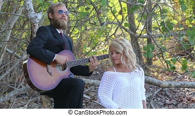 guitarist plays sitting on branch blonde girl poses at trees