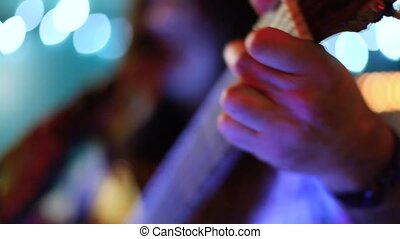 Guitarist plays to bar patrons by night.