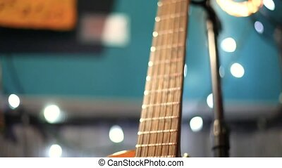 Close up footage of a traditional Spanish guitar standing on a small stage inside a local music bar. Ready for musician to play next set.