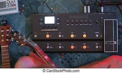 close-up guitarist tunes sound mixer for playing guitar to music lessons
