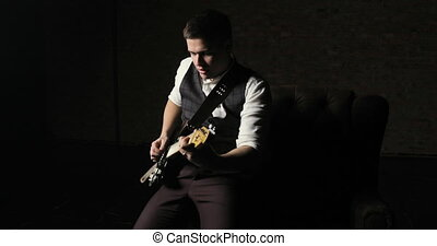 Guitarist sitting on armchair and playing solo on guitar -...