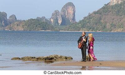 guitarist stands playing blonde girl walks around dancing