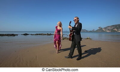 guitarist starts to play masterly blonde girl near on beach