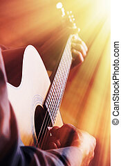 Guitarist playing on acoustic guitar in front of the light