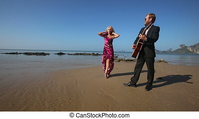 guitarist stops playing  blonde girl in red flirts in low tide