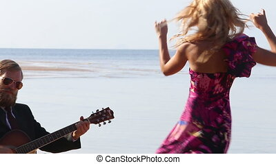 guitarist stops playing blonde girl stops dancing on beach