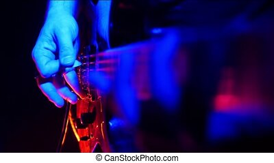 Guitarist tunes and start playing on his guitar in bright neon lighting.