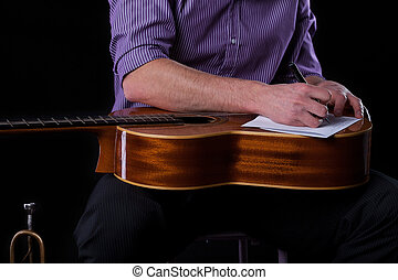 Close-up of a guitarist writing a song, horizontal