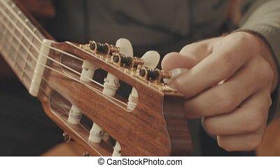 Guitarist's hands tuning guitar close-up 4K