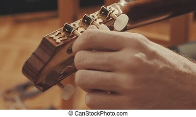 Guitarist's hands tuning guitar close-up