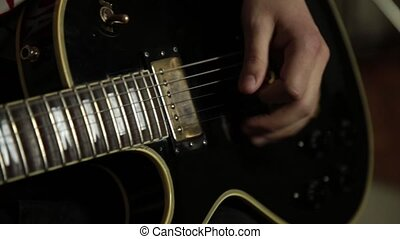 guitarists of a rock band plays on guitar, close-up hands and guitar neck