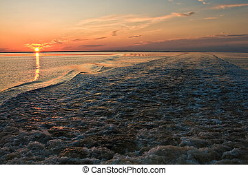 Sunset against the wake of a fishing boat in the Gulf of Mexico.