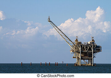 Gulf of Mexico oil rig against a cloudy blue sky.