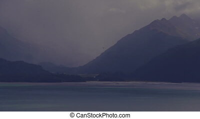 A solitary sea gull winging its way over Kachemak Bay on a cloudy, rainy afternoon, in slow motion.