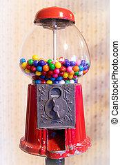 A gum ball machine with gum balls in it.